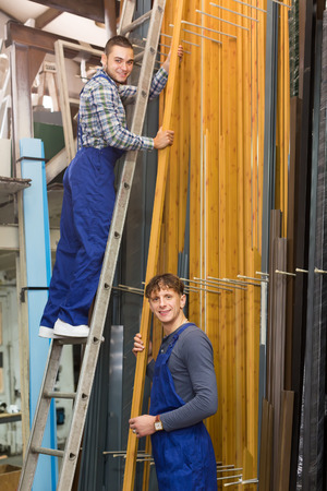 toolroom: Two workers choosing PVC window  frames at stand