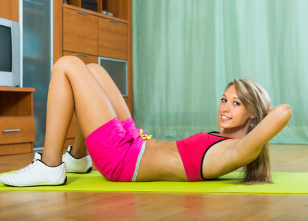 house trained: Attractive smiling girl working out on exercise mat at home