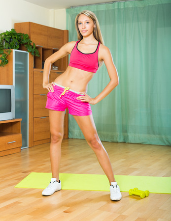 house trained: Positive young slender girl working out with dumbbells at home