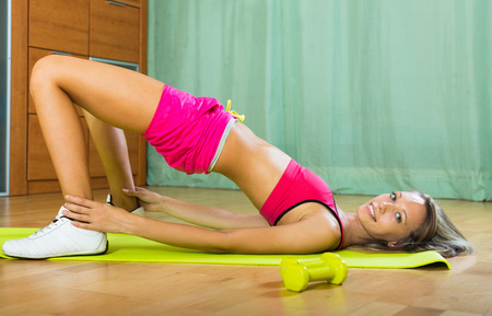 girl working out: Cheerful young sporty girl working out with dumbbells at home Stock Photo