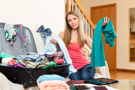 disarray: Smiling woman with clothes in hands sitting near opened overfull suitcase Stock Photo
