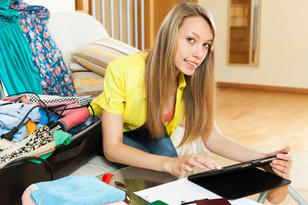 young leave: young woman  browsing places to visit with tablet before going on leave in home interior Stock Photo
