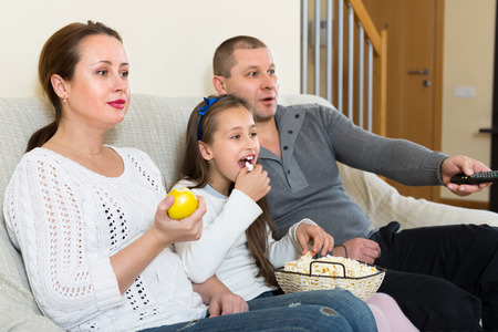tv show: Parents and cute girl watching TV show and smiling indoors. Focus on woman
