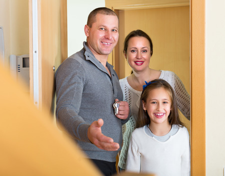 hypothec: Husband, wife and daughter coming inside mortgage house. Focus on girl