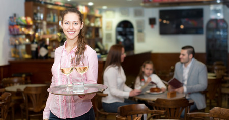 waitress and cheerful family with young daughter reading menu photo