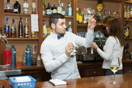 barmen: Waitress and barmen working in modern bar. Focus on man Stock Photo
