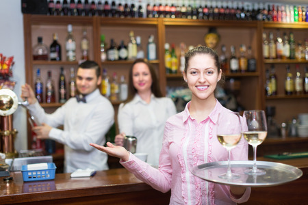 barmen: Happy young waitress and barmen working in modern bar