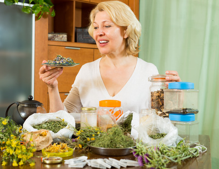 officinal: Smiling senior mature woman sitting at table with aroma herbs in home Stock Photo