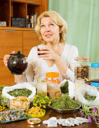 concoct: mature woman with dried herbs brewing herbal tea at home Stock Photo