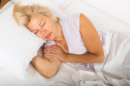 Blonde mature female sleeping on white pillow in bed at home photo