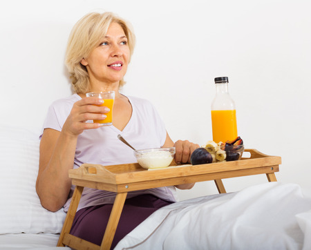 Mature woman eating orange juice, berries and yogurt at overbed table in bed photo