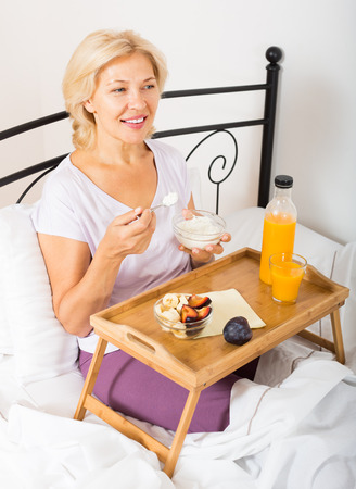 mature woman having yogurt with fruits for breakfast photo