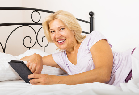 Happy mature woman with eBook laying in  bed at home photo