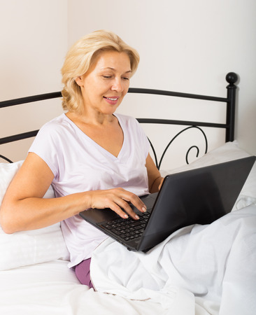 undress: Mature woman with laptop on white sheet in bed at home Stock Photo