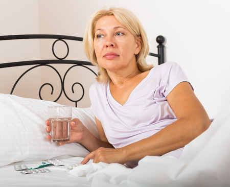 glass bed: Mature woman laying in bed with pills and glass of water in bed
