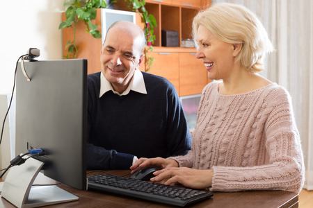 global retirement: Elderly couple set up a web camera for video calls at home