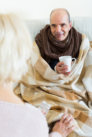 Mature wife is giving medicine to sick husband in scarf at sofa