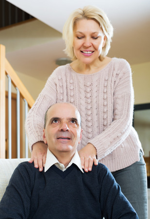 Happy pensioner sitting on sofa, smiling wife massaging his neck indoor Stock Photo