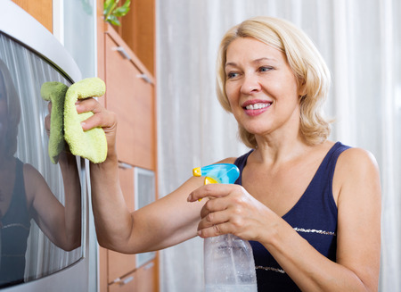 Happy mature woman  wiping the dust on TV in living room at home photo