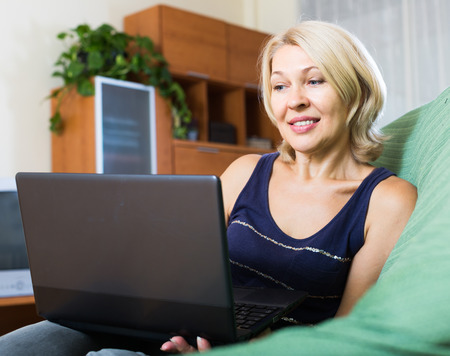 netbook: smiling mature woman using netbook on sofa in home