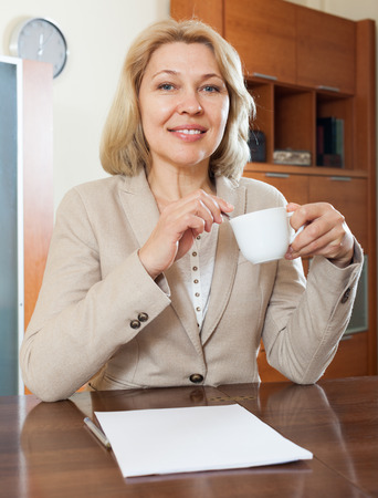 parsimony: mature businesswoman with financial documents at home or office interior