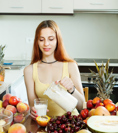 woman drinking milk: woman  drinking milk shake with fruits at home kitchen