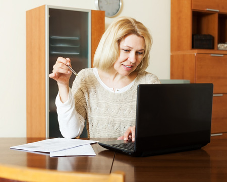 poorness: Working woman with notebook and financial documents at table at home Stock Photo