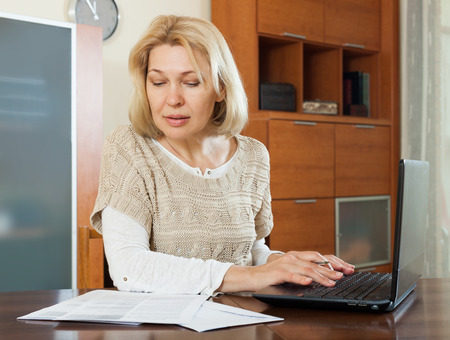 Woman staring financial documents with laptop  at table in home
