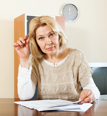 parsimony: mature woman filling in paper at home or office interior Stock Photo