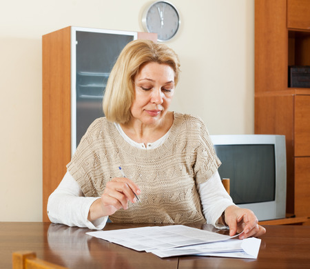 50 something fifty something: mature woman reading document at home or office