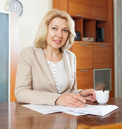 calculated: Portrait of mature businesswoman with financial documents Stock Photo