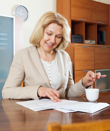 home office interior: mature woman with  documents and tea at table in home or office interior Stock Photo