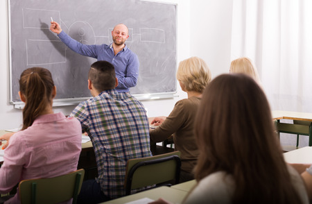 classroom: Attentive adult students with smiling male teacher in classroom Stock Photo