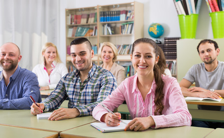 attentive: Attentive adult students industriously writing down summary in classroom