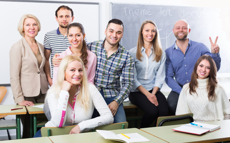 cohesive: Portrait of friendly teacher and adult students in classroom Stock Photo