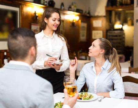 Portrait des adultes heureux ayant le dîner et le serveur respectueux