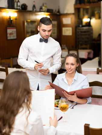 Young couple of girls eating out in a restaurant while handsome waiter is serving them
