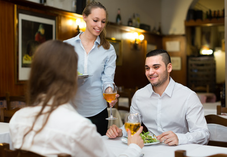 guests: Smiling female waiter serving guests table in restaurant Stock Photo