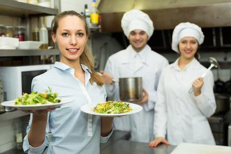 Deux chefs et serveur femme au restaurant cuisine. Mise au point sélective