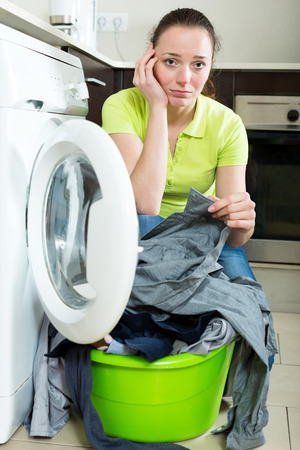 dirty clothes: Unhappy girl with dirty clothes near washing machine Stock Photo