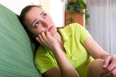 dark haired woman: Lonely dark haired woman in green t-shirt sitting on a couch at home and looking at the ceiling