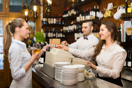 bartenders: Positive female drinking wine at counter and chatting with bartenders inside Stock Photo
