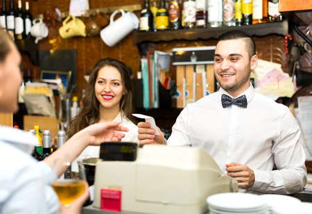 bartender: Joyful staff working in a bar: female bartender is smiling, male barista is handing over a check to a waiter