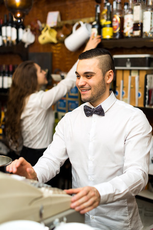 checkout counter: Male bartender working at the bar is standing next to a checkout counter Stock Photo