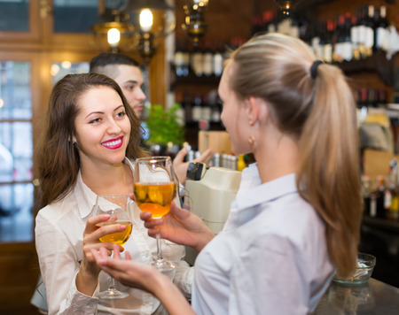 acquaintance: Casual acquaintance of smiling young happy adults at bar. Selective focus on girl