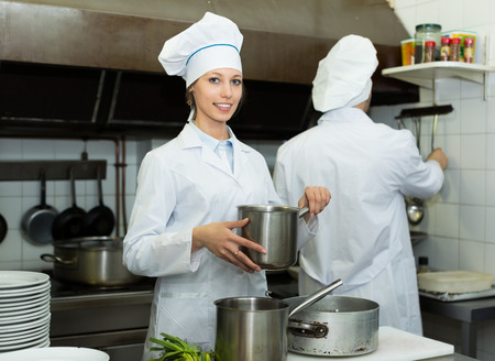 Positive smiling chef and assistant preparing meal in cafe photo