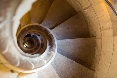 backstairs: Close up view at  stone spiral stairway indoors