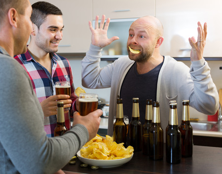 Laughing: Three men drinking beer and laughing at house party