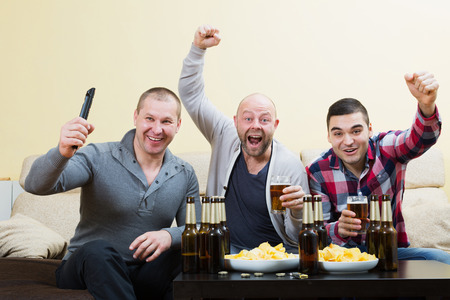 fandom: Three male friends sitting at table with beer and commenting sport tv channel Stock Photo