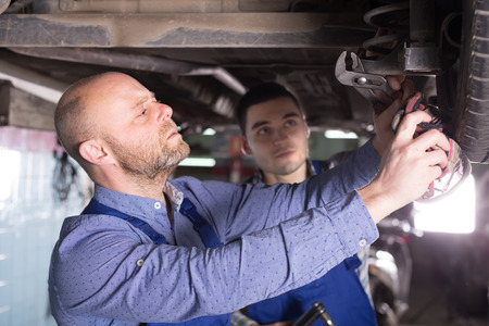 mounting holes: Car mechanics checking up pressure in tires at workshop